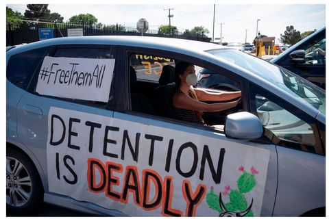 "Protest against Detention. Woman in car with two signs reading ""Detention is Deadly"" and ""Free Them All"""