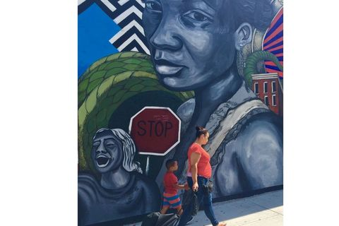 A Latinx mother and child with bright red shirts walk past wall-high mural with Black Latinx woman and child.