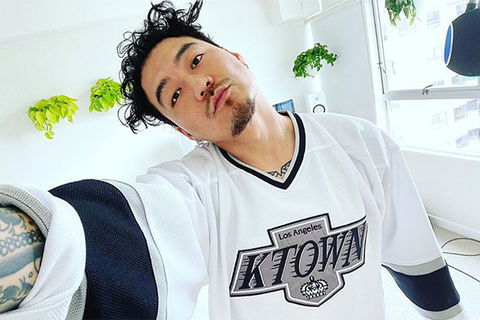 Dumbfoundead. Asian-American man with dark hair wearing K Town white and black jersey.