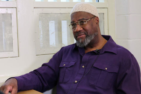 Jalil Muntaqim. Older Black man wearing white kufi and purple shirt and glasses.