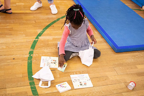 Literacy. Small Black girl with braids wearing a pink top and blue strip dress kneels on gym floor around papers.