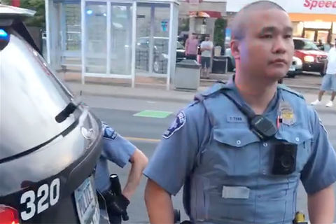 Asian police officerwith a shaven head wearing a blue uniform standing in front of a black police cruiser.