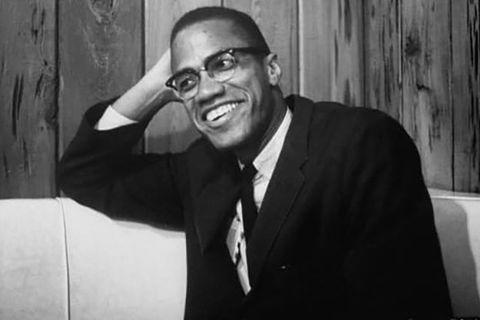 Malcolm X. Archival black and white photo of Black man wearing dark suit, white shirt and black tie.
