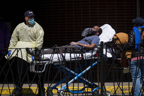 NYC-COVID-19. Male healthcare worker wearing blue baseball cap, blue face mask and yellow PPE coat wheels in a Black male patient on a stretcher who is wearing a blue Tee shirt and blue pants.