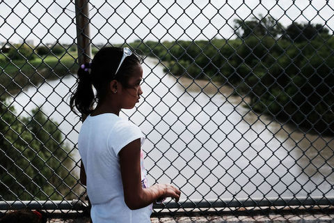 Young girl with dark hair stands in front of a wire fence that overlooks a stream of water.