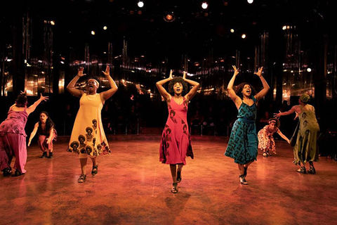 """for colored girls."" Seven women of color on stage dressed in blue, orange, brown, red, yellow, green and purple."