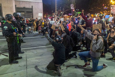 Protesters kneel before a group of armed police officers.