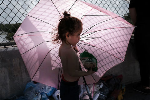 A small child stands shirtless in front a wire fence as she holds an open, pink umbrella.