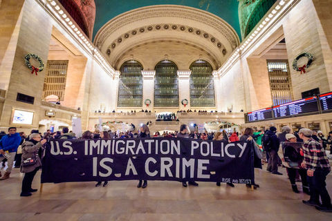 Protestors inside a large train station hold a giant sign that reads, U.S. Immigration Policy is a Crime