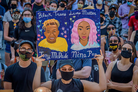 Black Trans Lives Matter rally. Man in a crowd holds up colorful drawing of Tony McDade and Nina Pop.
