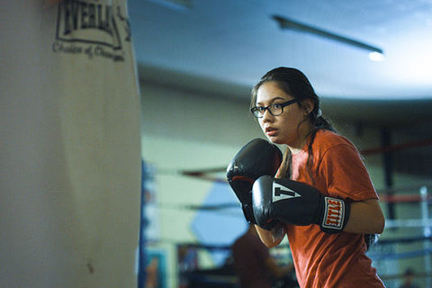 Donna Kipp. Young Blackfeet woman with dark hair, wearing glasses, orange Tee,  black boxing gloves standing in front of a body bag.