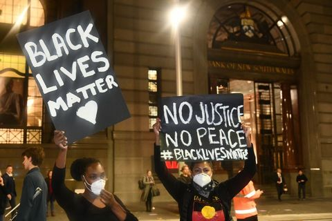 "Two young black women holding ""Black Lives Matter"" and ""No Justice, No Peace"" wearing black shirts and masks."