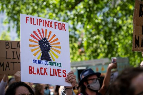 "A protester holds a homemade sign that says, ""Filipinx For Black Lives No Justice No Peace"" with a black power fist and rainbow coming out from the center of the fist"