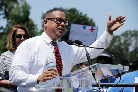 Keith Ellison. African American man with glasses, white shirt and red tie, at podium during the day