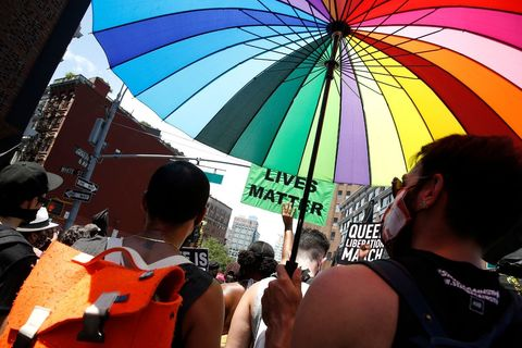 Pride Parade. Person standing with a multi-colored rainbow umbrella.