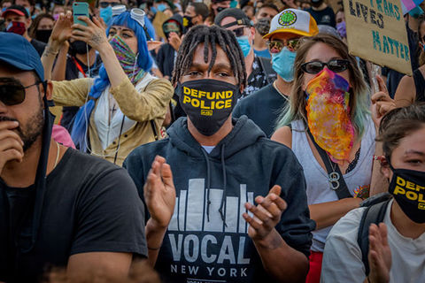 "Defund Police. Black male protestor in a crowd wearing a black face mask that reads ""defund police"" in yellow letters, wearing a black hoodie."