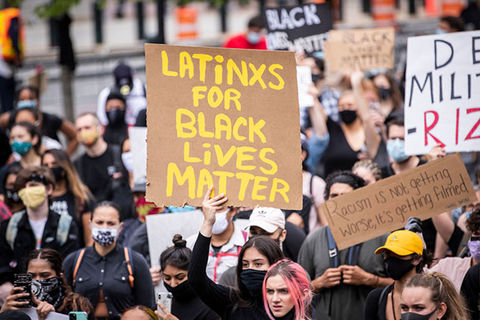"Latinx for BLM. Crowd of protestors where one woman holds up sign with yellow letters reading: ""LATiNXS FOR BLACK LiVES MATTER"""