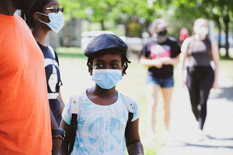 Little girl mask. Young Black girl wearing surgical mask, blue hat and white tee.