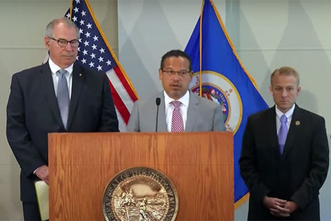 MPD Charges. Black man wearing glasses and gray suit stands in front of podium next to two White men wearing black suits.