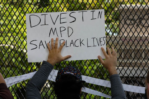 "protester hold a sign that reads, ""Divest in MPD"""