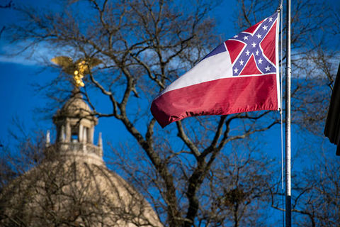 Mississippi Flag. Flag flying in the foreground with the capitol dome in the background.