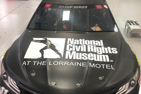 "NASCAR. Black car with hood reading ""National Civil Rights Museum at the Lorraine Motel"" and a logo."