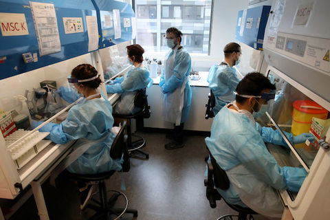 Researchers wearing blue protective gear sit and work in scientific lab.