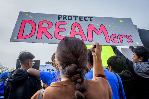 "A woman with a long braid holds a sign that reads, ""Protect Dreamers"""