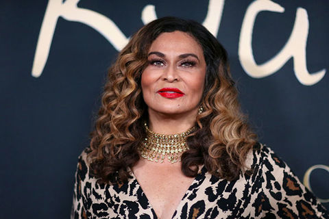 Tina Knowles. Black woman with long wavy blonde hair wearing a gold choker and black and brown top.