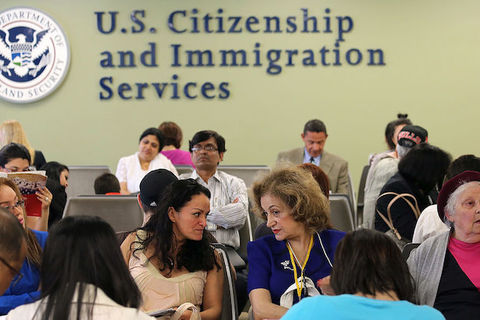 A group of people are seated below a large sign on a wall that reads, U.S. Citizenship and Immigration Services.