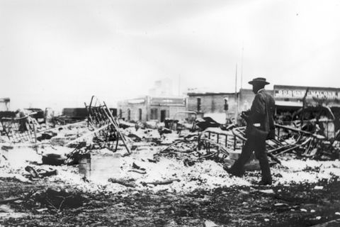 An African-American man with a camera looks at the skeletons of iron beds which rise above the ashes of a burned-out block after the Tulsa Race Massacre, Tulsa, Oklahoma, June 1921