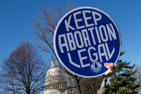 "A hand holds a sign that reads ""Keep Abortion Legal"" in front of the US Capitol and under a clear blue sky"