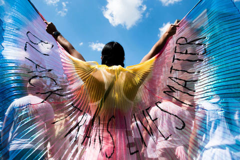 A person holding multicolored wings that read Black Trans Lives Matters outside under a blue sky.