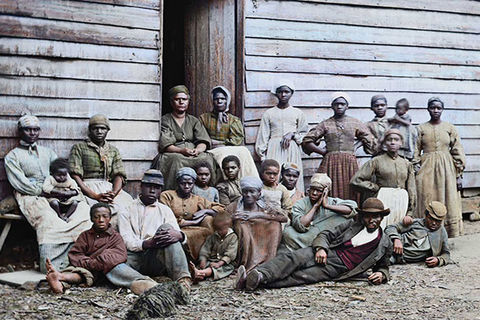 Black people. An archival photo showing more than a dozen Black people of various ages and gender in front of a cabin.