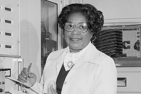 Mary Jackson. Black and white photo of Black woman with dark hair wearing white lab coat and glasses, holding a notepad and pen.