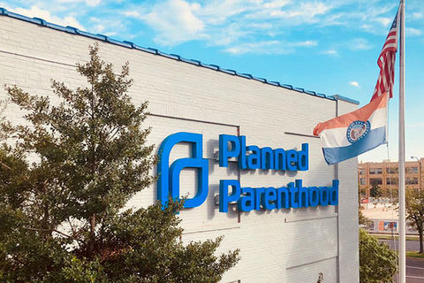 Planned Parenthood. Exterior of building with blue letters and logo reading Planned Parenthood next to a flying American flag.