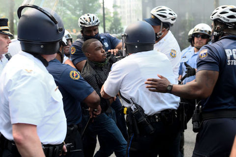 A Black man wearing a black shirt is struggling with at least seven police officers as they surround him.