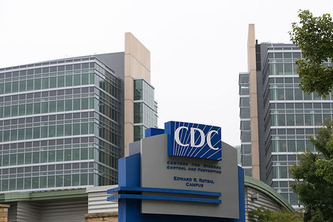 Center for Disease Control. Building exterior showing  CDC logo on blue background surrounded by high-rise buildings.