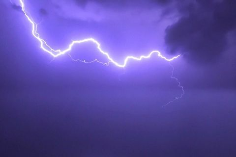 Deep purple sky with a bold streak of white lightning crossing throught