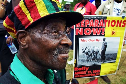 "Older Black man with a red, black, green, and gold ""rasta cap"" with brim, holding a ""Repaations Now!"" sign"