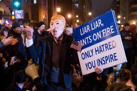 "Protest with a man with a Trump mask on with a long Pinnochio like nose and a sign reading ""Liar Liar, Pants on Fire Only hatred, you inspire"""