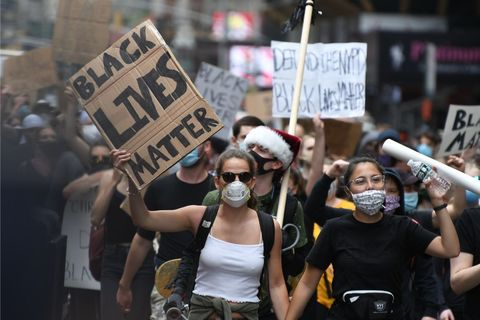 "Protest photo with two white women at the front both with masks on, one holding a sign saying, ""Black Lives Matter"""
