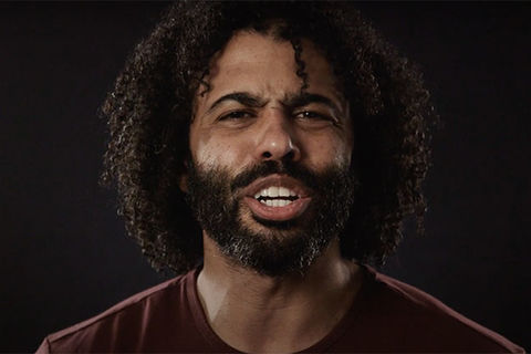 Daveed Diggs. Black man with dark curly hair and dark facial hair wearing a maroon colored top.