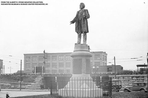 Frederick Douglass monument. Black and white photo of statue of a Black man on a tall pedestal in the city of Rochester, N.Y.