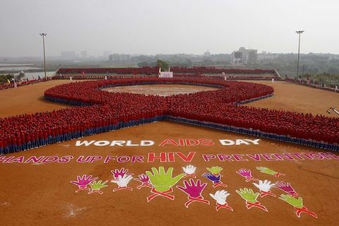 Aerial shot of people arranged as a red AIDS ribbon, as well as the words World Aids Day and Hands Up For HIV Prevention