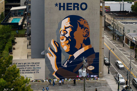 John Lewis mural. Mural of Black man with bald head wearing a suit with the words HERO above his head.