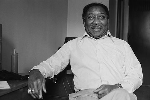Muddy Waters. Black and white archival photo of Black man with short dark hair wearing white shirt and tan pants.
