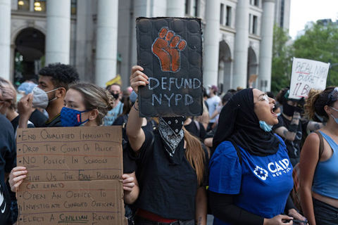 "A protester with a scarf covering his face is seen displaying placard reading ""Defund NYPD"""