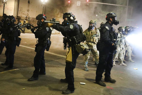 federal officers point large black weapons at protesters
