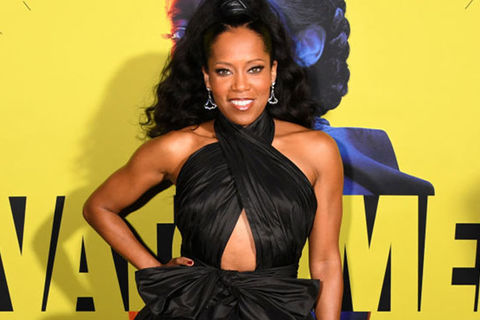 Regina King. Black woman wearing Black gown with long black hair poses in front of Watchmen poster.